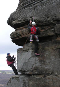 John helping a leader on Froggatt Pinnacle. Photo: Tony Stock